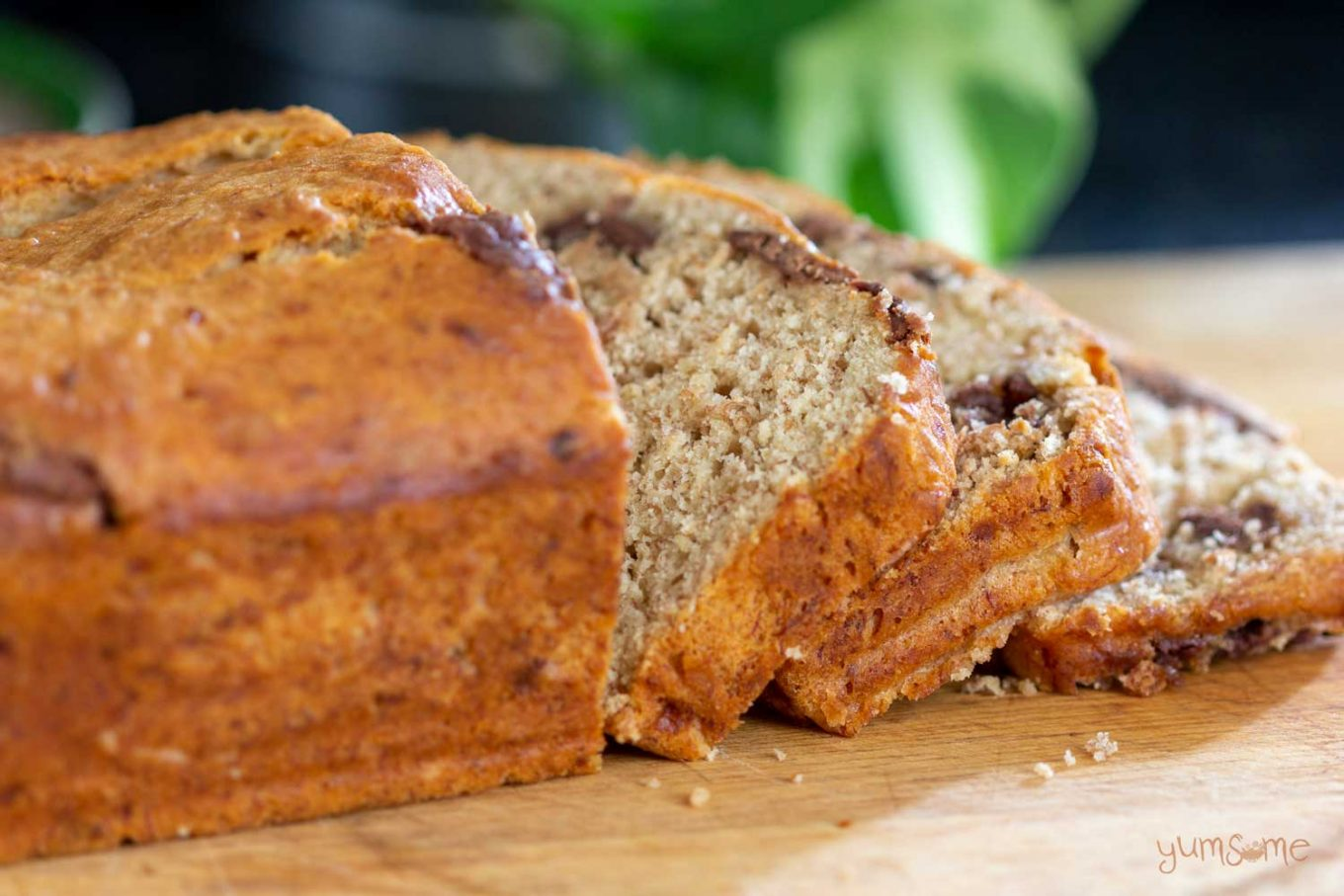 A loaf of chocolate chip banana bread on a wooden board.