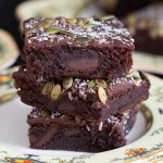 Closeup shot of three fudge brownies in a stack on a yellow plate.