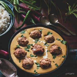 A skillet of malai kofta, plus silver spoons and chillies on a table.