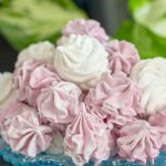 A pile of fluffy pink and white vegan marshmallows on a blue plate, with a green background.